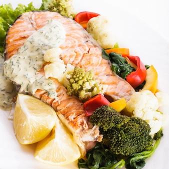 Un pavé de saumon grillé avec une sauce aux légumes et au citron