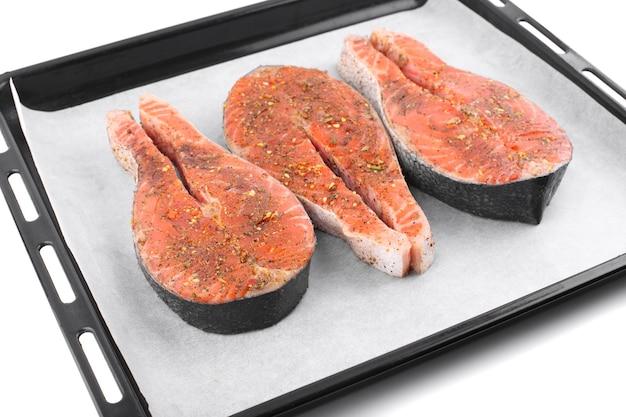 Pavé de saumon rouge aux épices sur papier parchemin blanc sur plateau noir