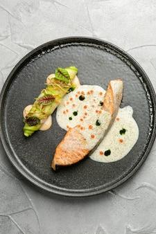 Pavé de saumon avec sauce sur plaque en céramique. saumon au four avec rouleau de courgettes et ingrédients sur table en béton