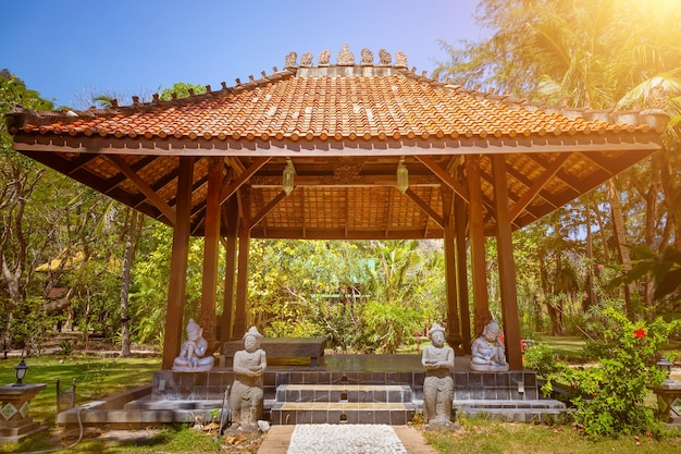 Pavillon de gazebo antique toit pagode de style asiatique été ensoleillé tropical gardenstone chemin statues