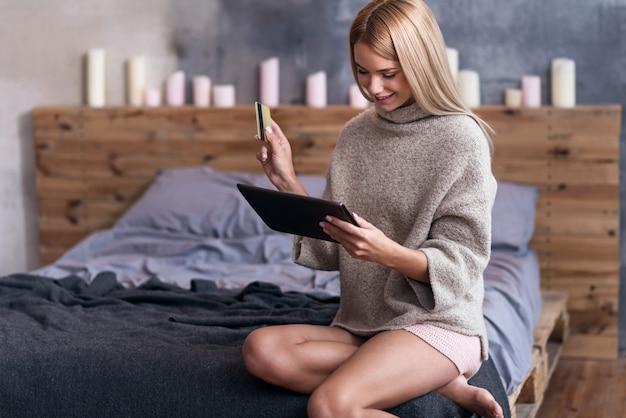 Payer pour ça. belle jeune femme ravie tenant une carte de crédit tout en utilisant la tablette et assis dans la chambre.