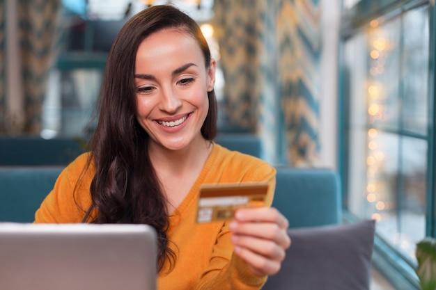 Payez n'importe où. jolie femme joyeuse joyeuse à l'aide de la carte de crédit tout en regardant vers le bas et en souriant