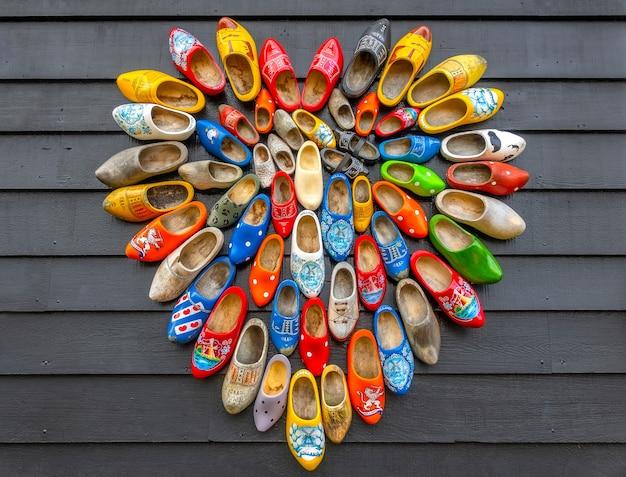Pays-bas. fond rugueux de planches grises. de nombreuses chaussures klomp nationales néerlandaises sont disposées en forme de cœur