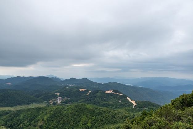 Un pays entouré de forêts par temps nuageux
