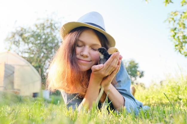 Pays style rustique, belle adolescente souriante avec des poulets nouveau-nés