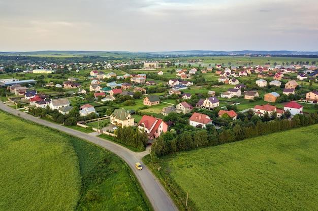 Paysage aérien d'une petite ville ou d'un village avec des rangées de maisons résidentielles et des arbres verts.