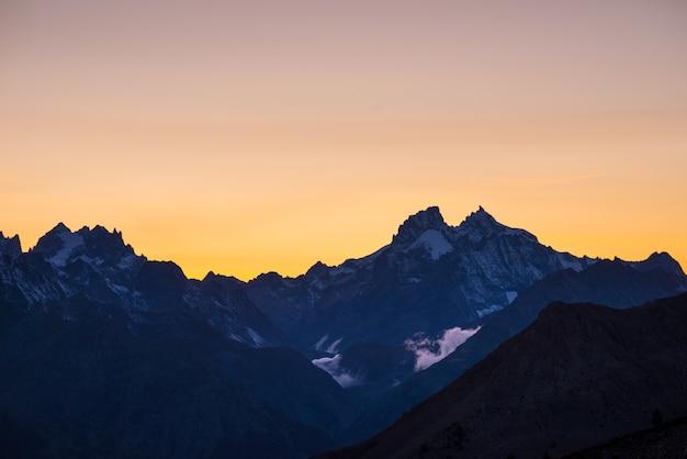 Paysage alpin d'altitude à l'aube avec premières lueurs des lumières sur le majestueux sommet de la barre des écrins