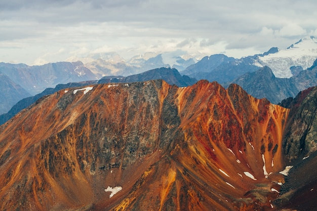 Paysage alpin atmosphérique avec des rochers rouges à l'heure d'or.