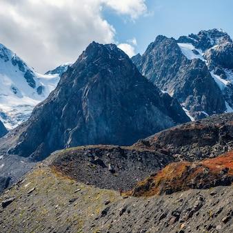 Paysage alpin enneigé de haute altitude avec sommet enneigé et rochers pointus sous un ciel bleu nuageux.