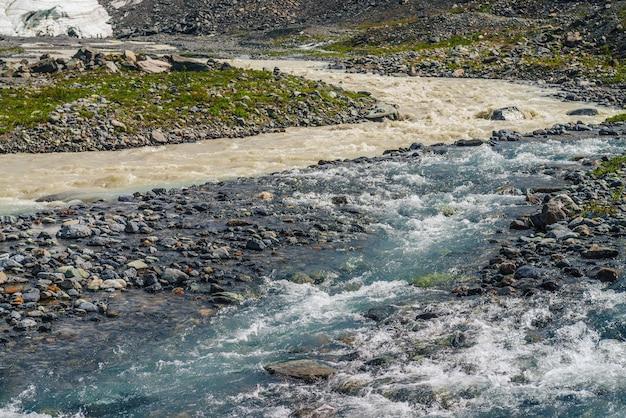 Paysage alpin ensoleillé au confluent de deux rivières de montagne différentes. une belle crique claire se jette dans une rivière sale. paysage de montagne coloré au confluent de deux rivières différentes parmi une flore riche.