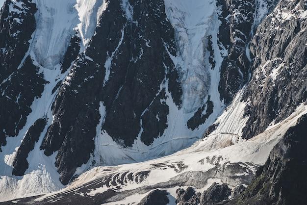 Paysage alpin texturé minimaliste atmosphérique de montagne rocheuse enneigée avec langue de glacier. fond de flanc de montagne enneigé. fissures sur la glace sur une pente raide. paysages majestueux en haute altitude.