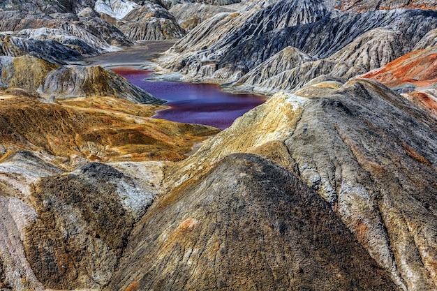 Paysage apocalyptique comme une surface de la planète mars. vue fantastique sur le lac rouge cramoisi. surface de la terre noire rouge-brun solidifiée.