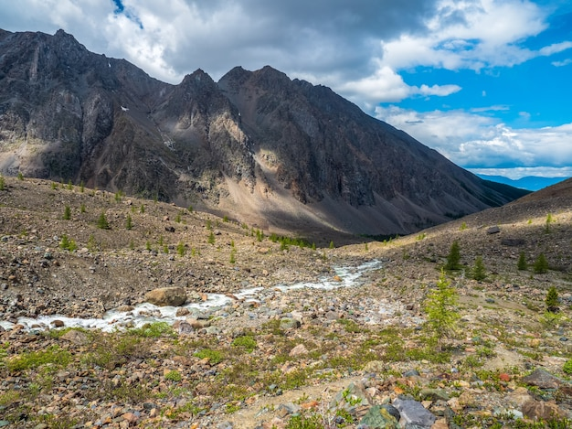 Paysage atmosphérique alpin ensoleillé avec ruisseau de montagne parmi les moraines par temps ensoleillé.