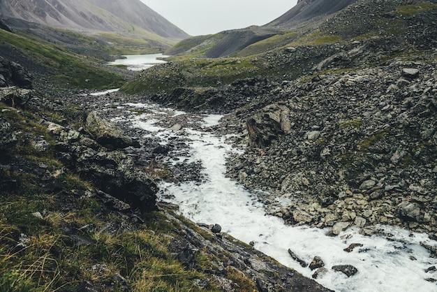 Paysage atmosphérique avec lac de montagne et ruisseau de montagne parmi les moraines par temps de pluie. paysage sombre et couvert avec rivière laiteuse et lac parmi les rochers. vue sombre sur la rivière et le lac de la montagne laitière.