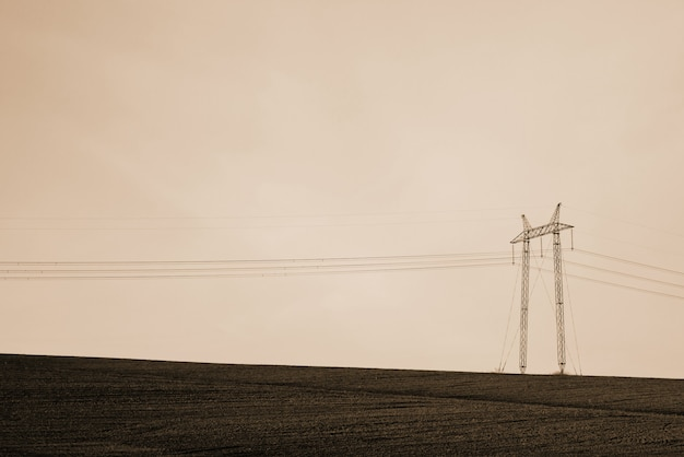 Paysage atmosphérique avec des lignes électriques dans le champ sous le ciel dans des tons sépia.