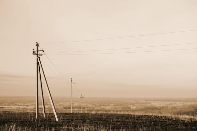 Paysage atmosphérique avec des lignes électriques dans le champ sous le ciel en tons sépia. image de fond des piliers électriques avec la surface. fils de haute tension au dessus du sol. industrie de l'électricité en monochrome.