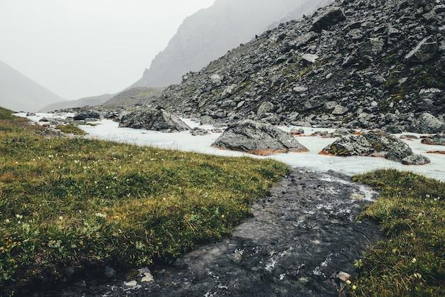 Paysage atmosphérique avec un ruisseau d'eau claire se jette dans la rivière de montagne parmi les moraines par temps de pluie. paysages sombres avec rivière laiteuse parmi les rochers. un ruisseau d'eau claire se jette dans la rivière de montagne de lait.