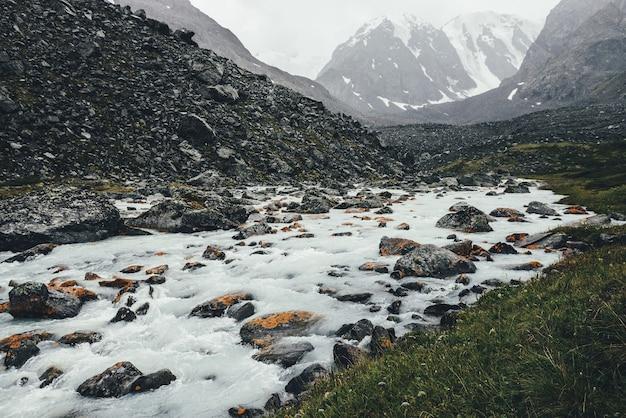 Paysage atmosphérique avec ruisseau de montagne parmi les moraines par temps de pluie. paysages sombres avec rivière laiteuse des montagnes enneigées. des pierres avec de la mousse et du lichen dans un cours d'eau. rivière de montagne parmi les rochers.
