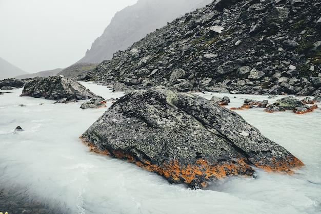 Paysage atmosphérique avec ruisseau de montagne parmi les moraines par temps de pluie. paysages sombres avec rivière laiteuse parmi les rochers. vue sombre sur la rivière de montagne. des pierres avec de la mousse et du lichen dans un ruisseau d'eau de lait.