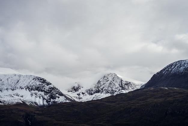 Paysage atmosphérique sombre avec des montagnes enneigées sous un ciel gris nuageux.