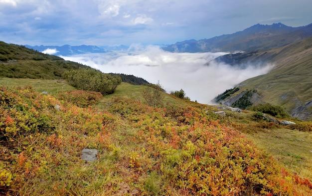 Paysage automnal dans la montagne des alpes avec buisson rouge et nuages dans la vallée- col du petit saint bernard