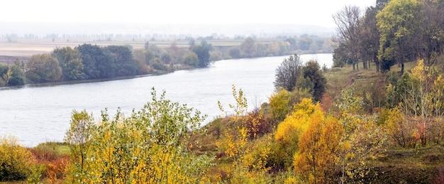 Paysage d'automne avec des arbres et des buissons colorés sur la rive, rivière et forêt au loin, panorama. automne doré