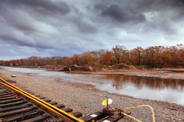 Paysage d'automne au coucher du soleil avec des collines et des nuages de ciel de rivière déversements d'eau de tempête
