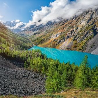Paysage d'automne coloré avec lac de montagne clair en forêt parmi les sapins au soleil. paysages lumineux avec un beau lac turquoise sur fond de hautes montagnes. lac inférieur de shavlin.