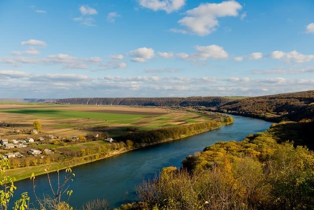 Paysage d'automne - rivière, ciel avec nuages, champs.