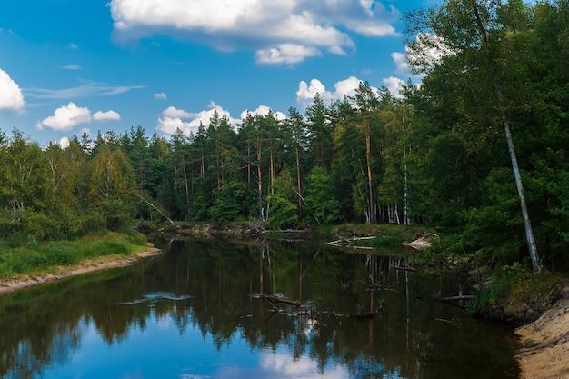 Paysage d'automne. la rivière coule à travers la forêt, ciel bleu avec des nuages.