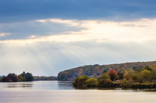 Paysage d'automne avec une rivière et des nuages pittoresques à travers lesquels pénètrent les rayons du soleil