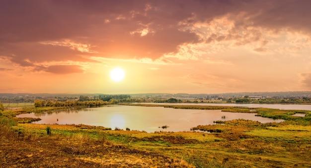 Paysage d'automne à vol d'oiseau avec végétation et rivière au coucher du soleil