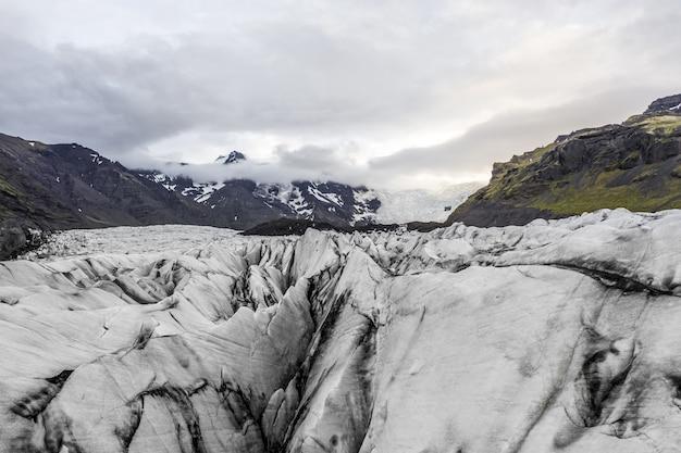 Paysage de badlands couverts de glace sous un ciel nuageux en islande