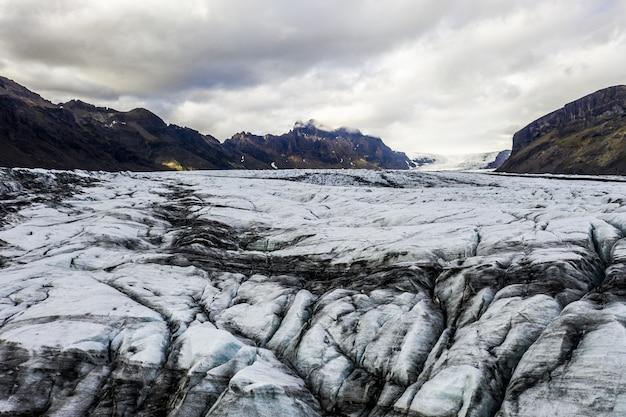 Paysage de badlands recouverts de glace sous un ciel nuageux en islande