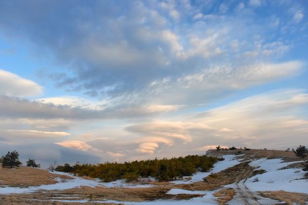 Paysage avec de beaux nuages lenticulaires dans les montagnes au coucher du soleil