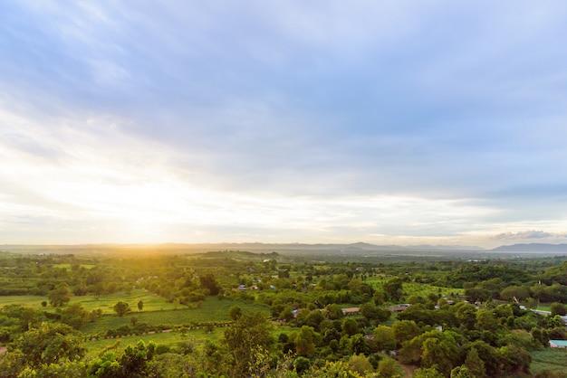 Paysage bleu et vert de nuages, montagne et forêt avec coucher de soleil le soir vu de dessus.