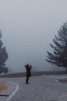 Paysage de brouillard brumeux dans une montagne. jeune femme prenant des photos. concept d'hiver ou d'automne