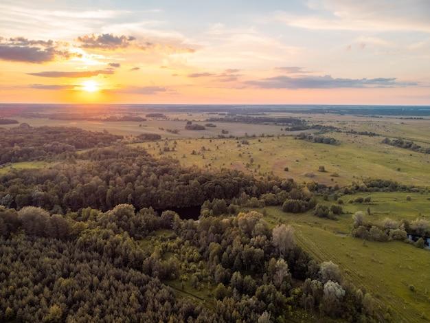 Paysage calme de forêts et de champs au coucher du soleil