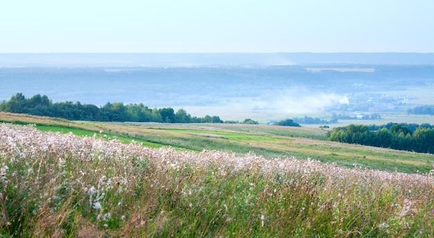 Paysage de campagne d'été avec village sur vallée