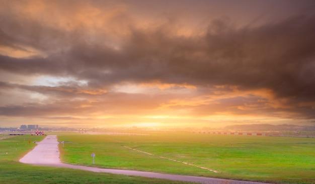 Paysage de champ d'herbe verte à l'aéroport piste floue avec le décollage d'un avion commercial