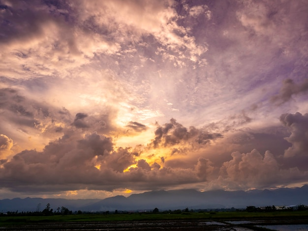 Paysage de ciel nuageux couvre la montagne et le champ de riz.