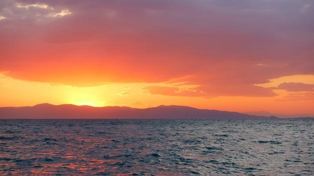Paysage avec un ciel rouge jaune brillant avec des nuages au-dessus de la mer au coucher du soleil. île d'égine, grèce