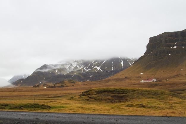 Paysage de collines couvertes de neige et d'herbe sous un ciel nuageux en islande