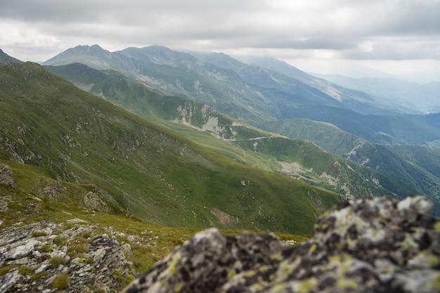 Paysage de collines couvertes de verdure avec des montagnes rocheuses sous un ciel nuageux sur l'arrière-plan
