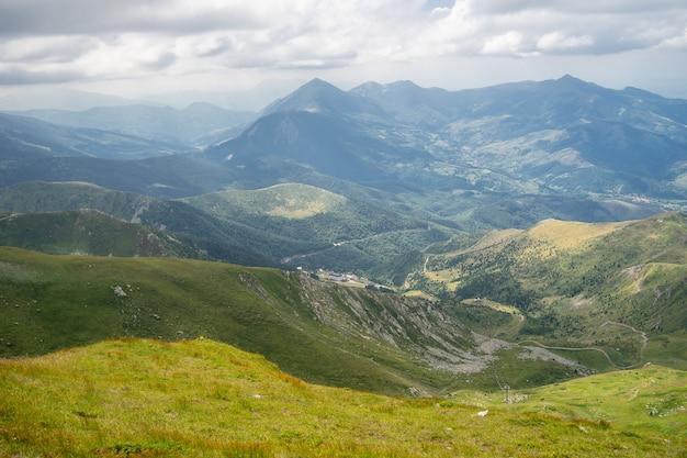 Paysage de collines couvertes de verdure avec des montagnes rocheuses sous un ciel nuageux