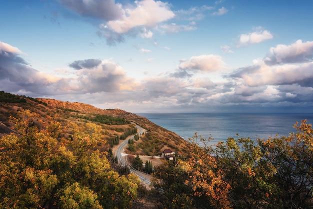 Paysage de collines, mer, ciel, nuages et route longeant la côte.
