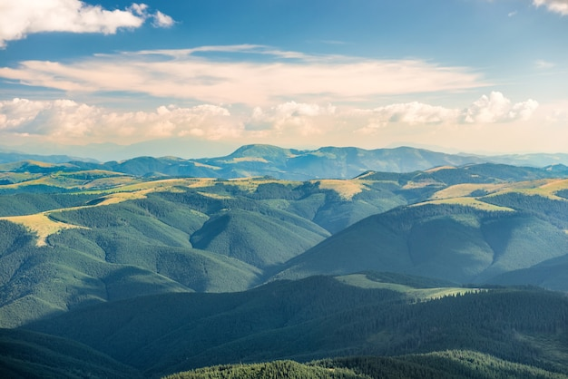 Paysage avec des collines verdoyantes et des nuages blancs sur le ciel au coucher du soleil
