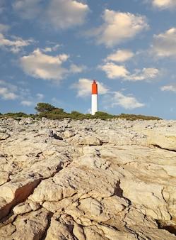 Paysage de côte de la mer rocheuse avec phare sur ciel bleu clair, low angle view
