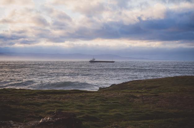 Paysage côtier avec bateau en arrière-plan.