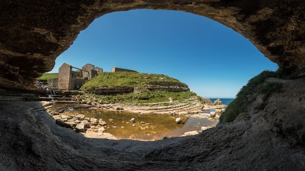Paysage côtier de l'embouchure d'une rivière dans la mer depuis l'intérieur d'une grotte
